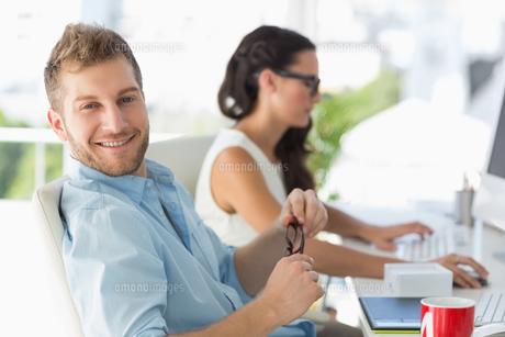 Attractive designer smiling at camera at deskの写真素材 [FYI00000212]