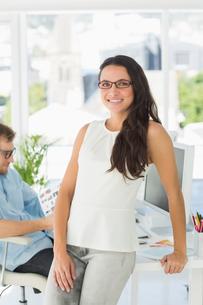 Brunette designer smiling at camera leaning on deskの写真素材 [FYI00000214]