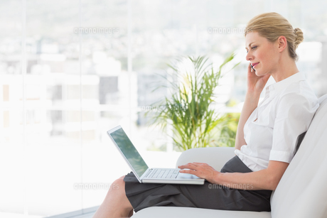 Businesswoman sitting on the sofa with laptopの写真素材 [FYI00000215]