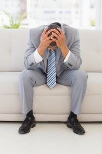 Stressed businessman sitting on couchの写真素材 [FYI00000216]