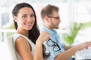 Beautiful designer smiling at camera at deskの写真素材 [FYI00000220]
