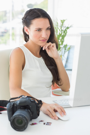 Focused photographer sitting at her desk using computerの写真素材 [FYI00000231]