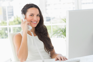 Beautiful businesswoman on telephone at her desk smiling at cameraの写真素材 [FYI00000235]