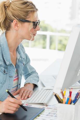 Blonde focused designer using digitizer at her deskの素材 [FYI00000249]