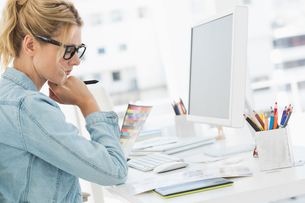 Blonde focused designer working at her deskの写真素材 [FYI00000259]