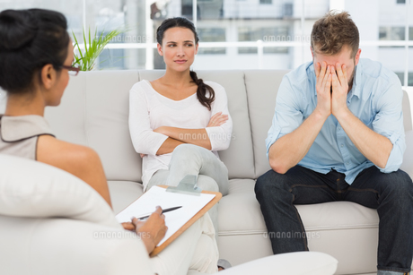Unhappy couple sitting on sofa at therapy sessionの写真素材 [FYI00000263]