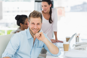 Handsome man smiling at camera while colleagues talk at deskの写真素材 [FYI00000264]