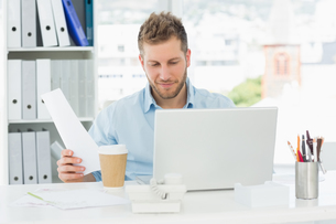 Happy man working at his desk on laptopの素材 [FYI00000268]