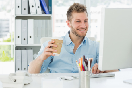 Smiling man working at his desk drinking a take away coffeeの素材 [FYI00000269]