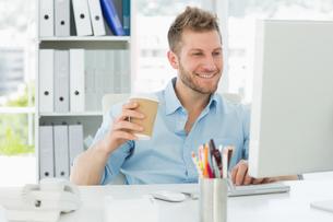 Smiling man working at his desk drinking a take away coffeeの素材 [FYI00000269]