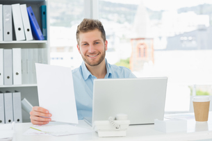 Handsome man working at his desk on laptop smiling at cameraの写真素材 [FYI00000270]