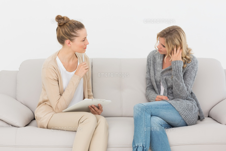 Upset woman talking to her therapist on the couchの写真素材 [FYI00000272]