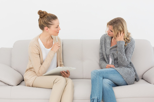 Upset woman talking to her therapist on the couchの素材 [FYI00000272]