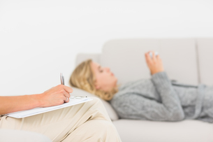 Therapist taking notes on her patient on the sofaの写真素材 [FYI00000281]