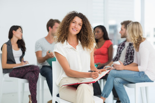 Smiling woman looking at camera while colleagues are talking behind herの写真素材 [FYI00000289]