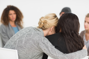 Women embracing in rehab group at therapyの写真素材 [FYI00000290]