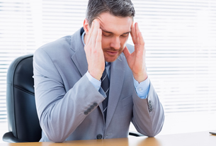 Businessman with severe headache sitting at office deskの写真素材 [FYI00000308]