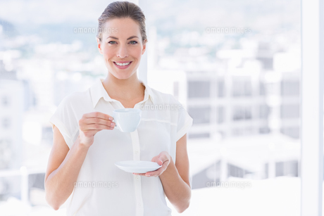 Smiling businesswoman with tea cup in officeの素材 [FYI00000317]