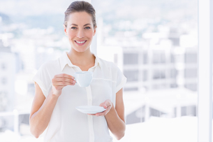 Smiling businesswoman with tea cup in officeの写真素材 [FYI00000317]