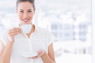 Smiling young businesswoman with tea cupの写真素材 [FYI00000318]