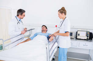 Doctors visiting a male patient in hospitalの写真素材 [FYI00000322]