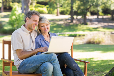 Couple using laptop on park benchの写真素材 [FYI00000329]