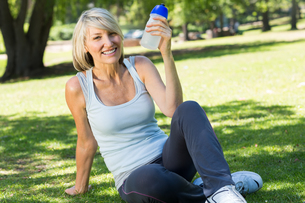 Relaxed woman holding water bottle in parkの写真素材 [FYI00000350]