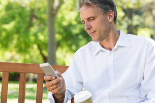 Businessman reading text message on mobile phoneの写真素材 [FYI00000352]