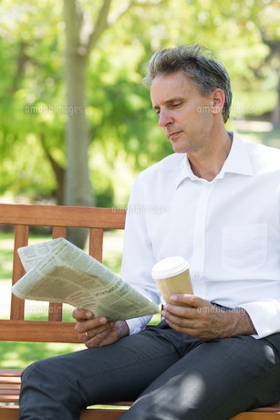 Businessman reading newspaper in parkの写真素材 [FYI00000355]
