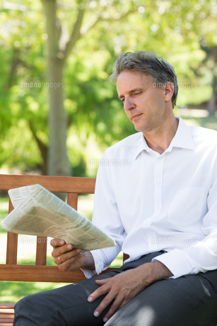 Businessman reading newspaper in parkの写真素材 [FYI00000356]