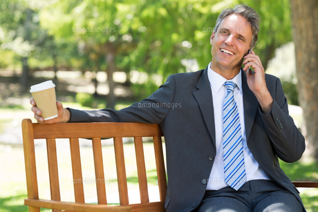 Businessman with disposable cup answering cellphoneの写真素材 [FYI00000361]