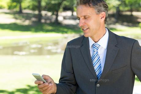 Businessman text messaging through cellphoneの写真素材 [FYI00000363]