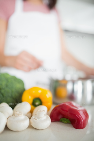 Vegetables with blurred woman preparing food in kitchenの写真素材 [FYI00000375]