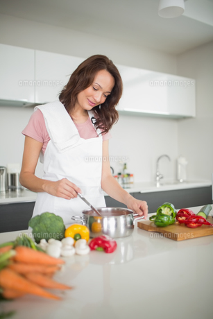 Smiling young woman preparing food in kitchenの素材 [FYI00000376]