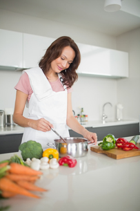 Smiling young woman preparing food in kitchenの写真素材 [FYI00000376]
