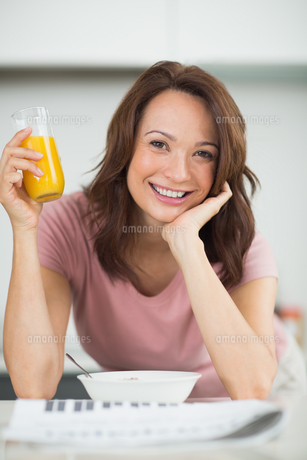 Woman with a bowl of cereals, orange juice and newspaper in kitchenの写真素材 [FYI00000380]