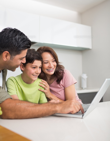 Smiling couple with son using laptopの写真素材 [FYI00000385]