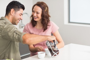 Happy man pouring tea to womans cup in kitchenの写真素材 [FYI00000386]