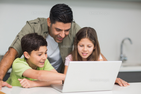 Father with young kids using laptop in kitchenの写真素材 [FYI00000388]