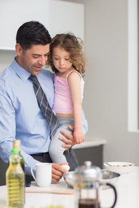 Well dressed father carrying his daughter while preparing foodの写真素材 [FYI00000389]