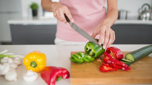 Mid section of a woman chopping vegetables in kitchenの写真素材 [FYI00000390]