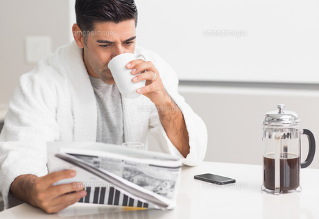 Man drinking coffee while reading newspaper in kitchenの素材 [FYI00000391]