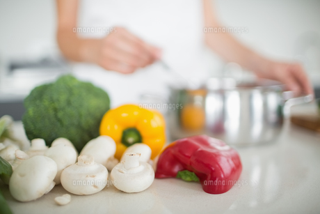 Vegetables with blurred woman preparing food in kitchenの素材 [FYI00000394]