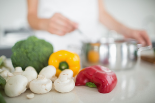 Vegetables with blurred woman preparing food in kitchenの写真素材 [FYI00000394]