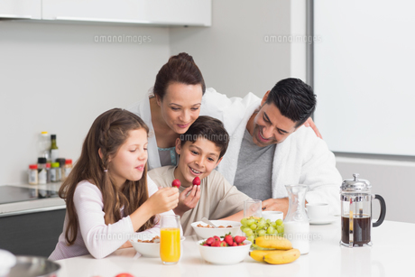 Happy kids enjoying breakfast with parents in kitchenの写真素材 [FYI00000395]