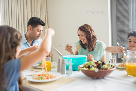 Family of four at dining table in the homeの写真素材 [FYI00000398]