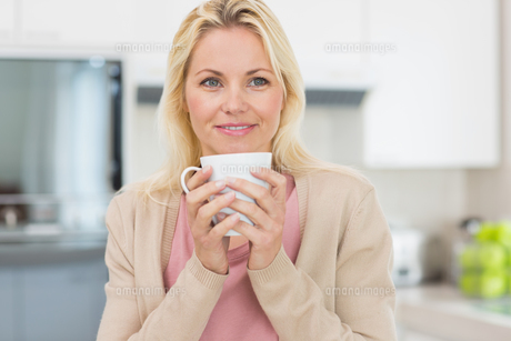 Beautiful young woman with coffee cup in kitchenの写真素材 [FYI00000399]