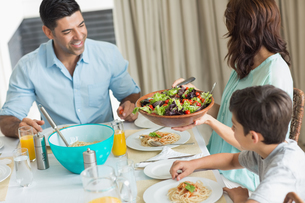 Happy family of three sitting at dining tableの写真素材 [FYI00000400]