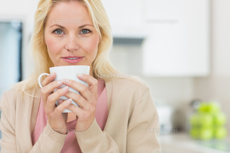Portrait of a beautiful woman with coffee cup in kitchenの素材 [FYI00000401]