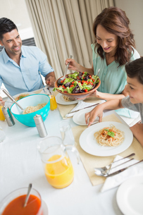 Happy family of three sitting at dining tableの写真素材 [FYI00000403]